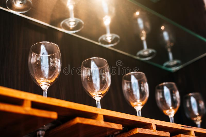 Drinking wine glasses shelf in restaurant with lighting showcase background. Many clean containers in restaurant or night pub and royalty free stock photos