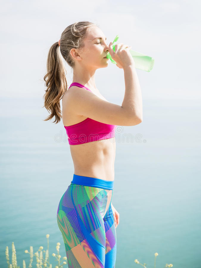 Drinking woman in uniform outdoors. Fitness girl on nature. Fitness girl on nature. Drinking woman in uniform outdoors stock images