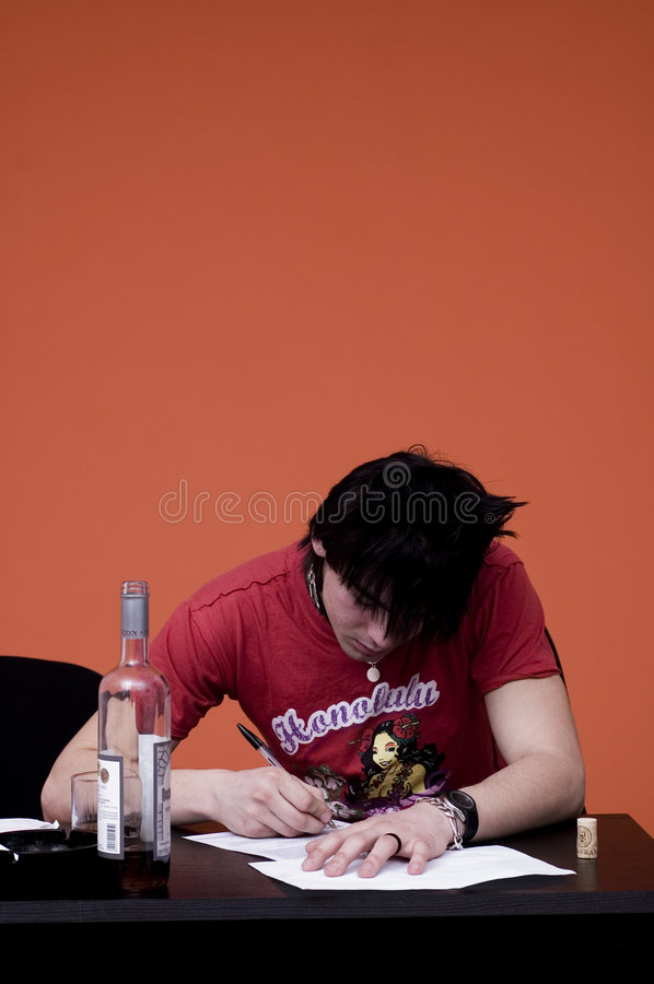 Drinking and Writing. Young man or teenager with bottle of liquor beside him, sitting at desk and writing or studying royalty free stock photography