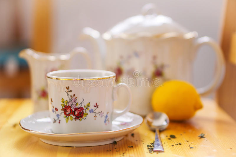 Drinks, relaxation and tea party concept - tea-set of cup, pot, spoon, lemon and saucer. Closeup stock image
