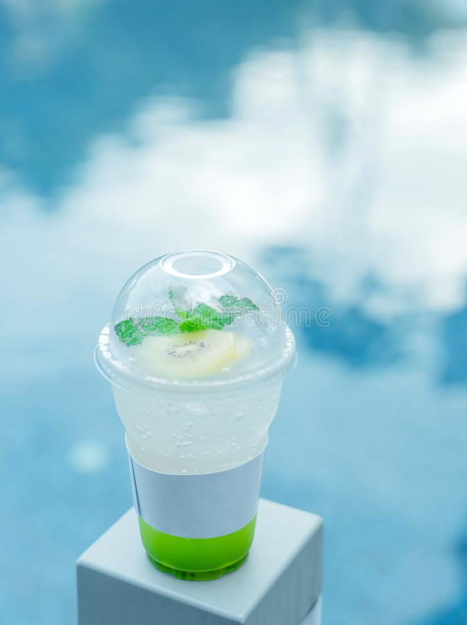 Drinks soda and Green apple served in a plastic cup on a natural background. Selective focus. Drinks soda and Green apple served in a plastic cup on a natural stock photo