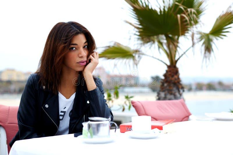 Drinkt de Afro Amerikaanse vrouw koffie en het genieten van van haar recreatietijd bij weekend stock foto