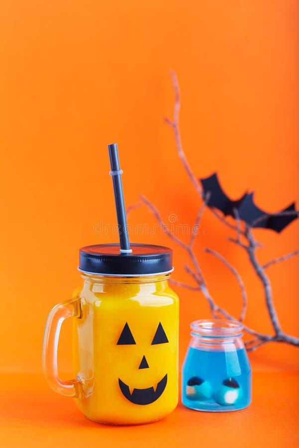 Drinkt de de gezonde pompoen of wortel van Halloween in de glaskruik met eng gezicht op een oranje achtergrond stock afbeeldingen
