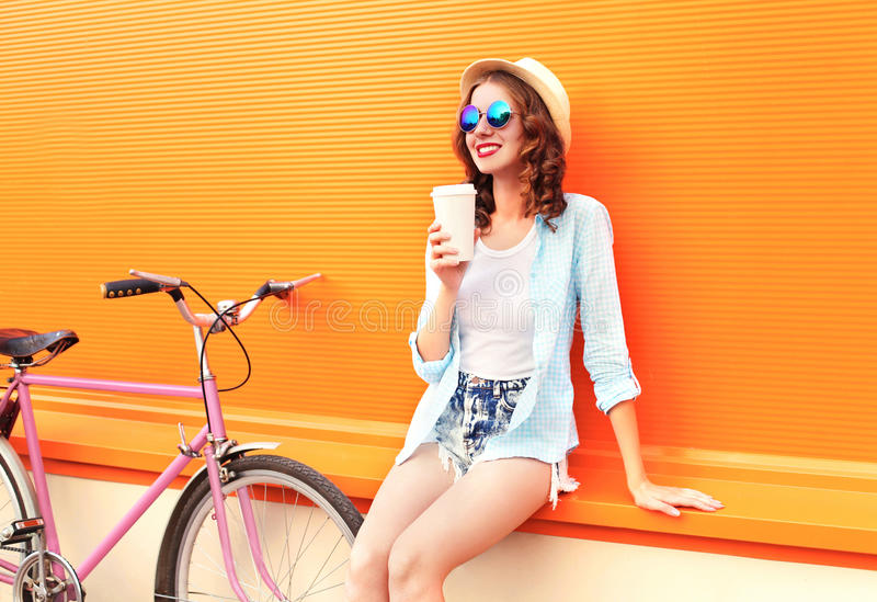 Drinkt de manier mooie vrouw koffie van kop dichtbij retro uitstekende roze fiets over kleurrijke sinaasappel stock fotografie