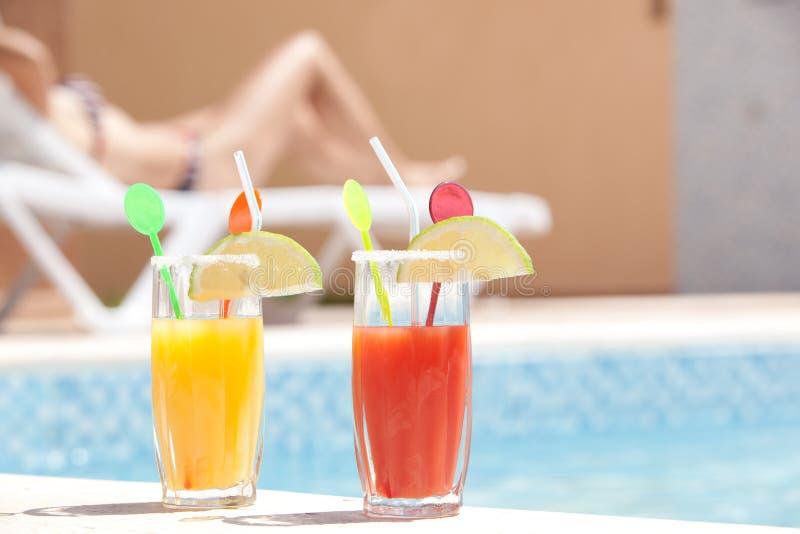 Drinkt dichtbij de pool met jonge vrouw zonnebadend I royalty-vrije stock afbeeldingen