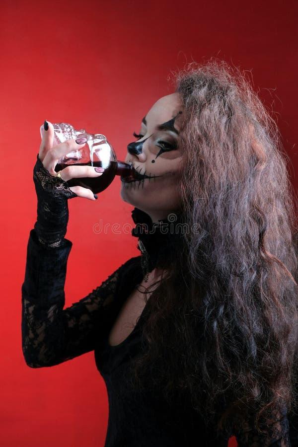 Drinkt een Halloween-Stijl brunette in zwarte kleren rode vloeistof die als bloed van een schedelkaraf kijkt Afschuwelijk meisje  royalty-vrije stock afbeeldingen
