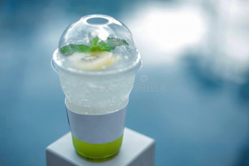 Drinkt soda en Groene die appel in een plastic kop op een natuurlijke achtergrond wordt gediend royalty-vrije stock afbeelding