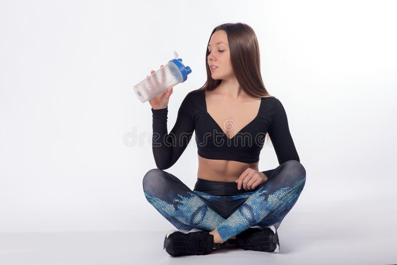 Drinkvatten för kvinnlig idrottsman nen från sportflaskan royaltyfria bilder