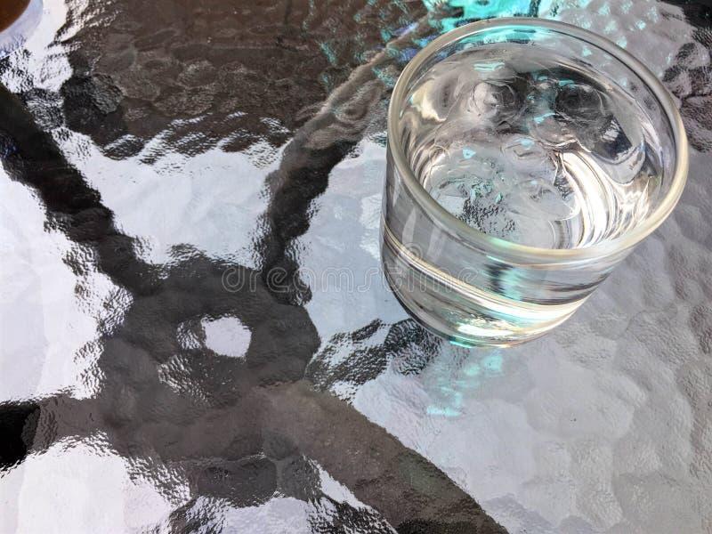 Drinkwater en ijs in glas op de lijst stock afbeelding
