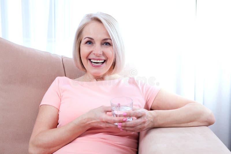 Drinkwater van de portret het mooie midden oude vrouw in de ochtend stock fotografie