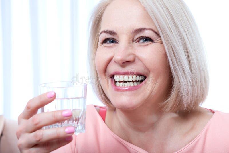 Drinkwater van de portret het mooie midden oude vrouw in de ochtend royalty-vrije stock afbeeldingen