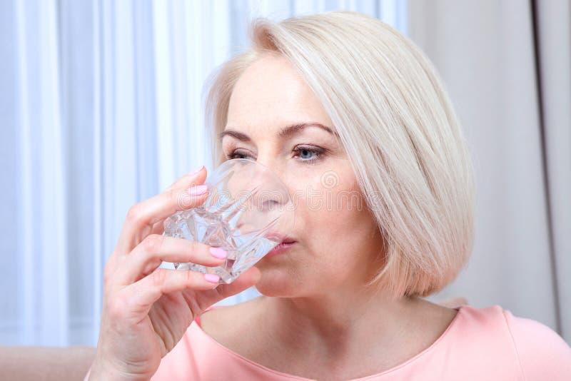 Drinkwater van de portret het mooie midden oude vrouw in de ochtend royalty-vrije stock fotografie