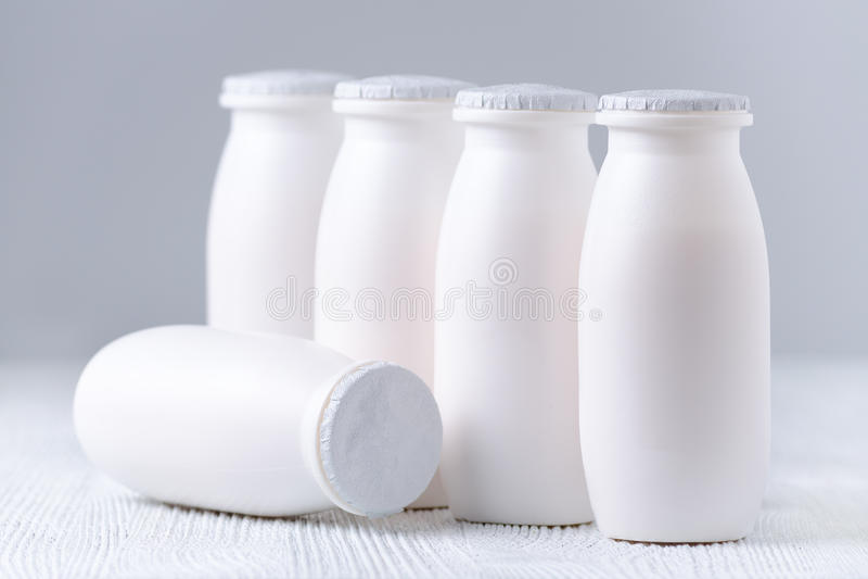 Drinkyoghurt i plast-flaskor på grå bakgrund royaltyfri foto