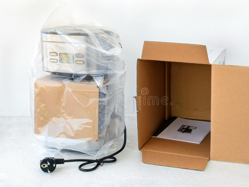 Drip-type coffee maker is in cellophane and near its cardboard box with instruction manual. Unpacking a new coffee machine. royalty free stock images