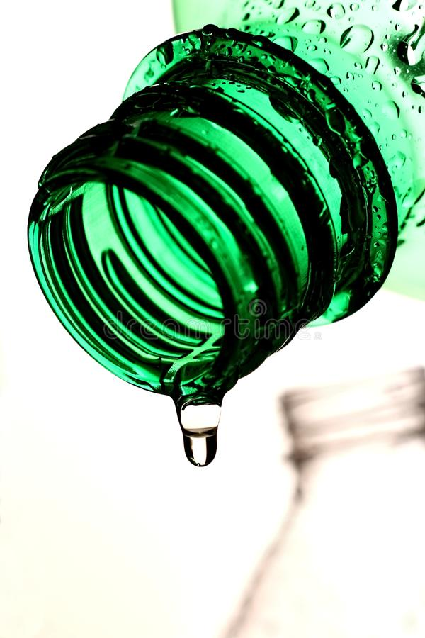 Dripping Bottle Abstract. Green plastic bottle with a clear liquid drip stock photo