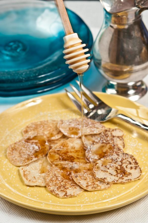 Dripping maple syrup over a stack of Johnny cakes royalty free stock images