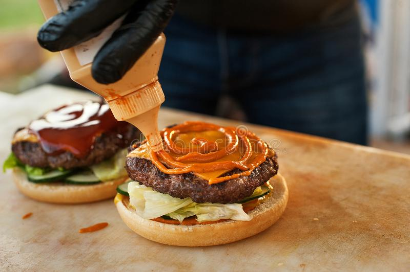 Dripping mustard on the burger. street fast food. stock image