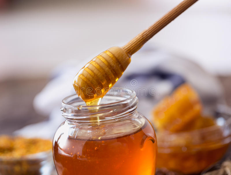 Dripping sweet honey from wooden dipper. Background royalty free stock photo