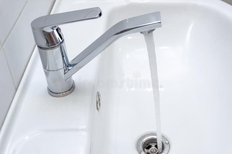 Dripping water from the single handle mixer tap mounted on a wash basin. Dripping water from the single handle mixer tap mounted on a white wash basin stock photo