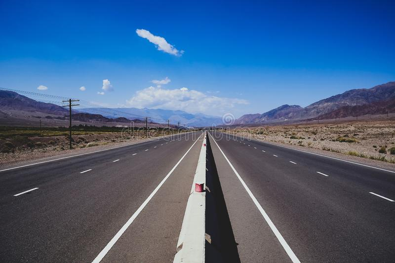 We drive along a long lonely highway to the snowy mountains. Endless road through a dry, dusty landscape. Riding along a long lonely highway into the snowy royalty free stock photo