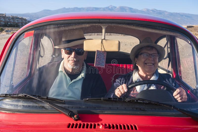 Elderly couple inside an old red car driving. Drive an old red car for two seniors men and woman, she smiles and he looks at you. Both with hat. Alternative royalty free stock photo