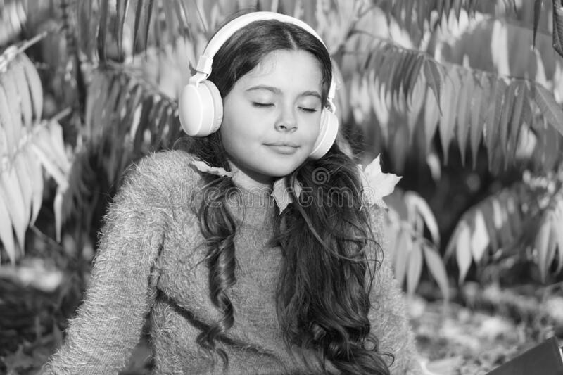 Drive by song. Enjoy music outdoors fall warm day. Audio file. Kid girl relaxing near autumn tree with modern wireless. Headphones. Music for autumn cozy mood royalty free stock photo