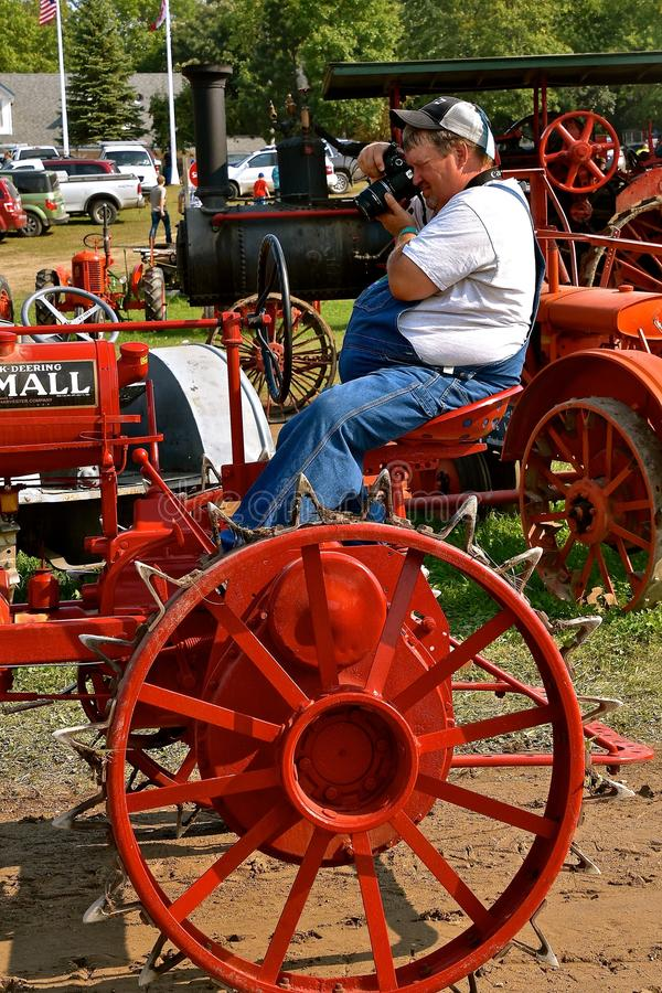 Driver driver acting as photographer. ROLLAG, MINNESOTA, Sept 2, 2017: An unidentified man photos his restored Farmall tractor during the daily parade at the stock image