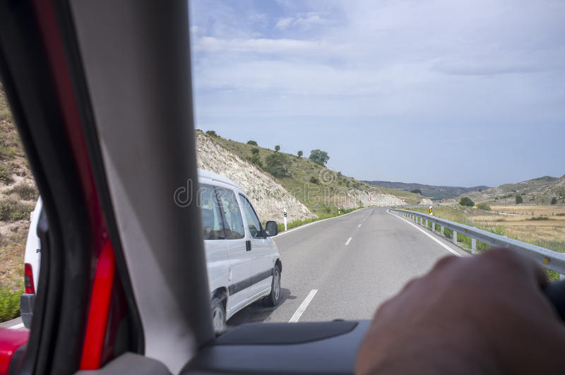 Driver being overtaken at local road. View from the inside of the car royalty free stock image