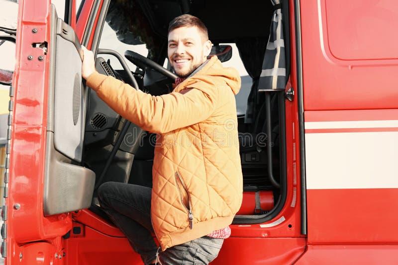 Driver bello vicino al grande camion moderno fotografie stock libere da diritti
