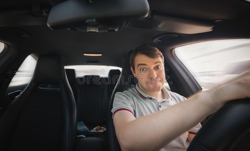 Driver in a car. Driver in a car with surprised face. Wide angle shot stock photos