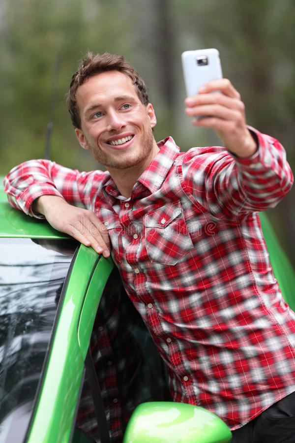 Driver by car taking selfie photo with smartphone. After driving in new green car. Happy man taking picture with smartphone camera during travel road trip royalty free stock image