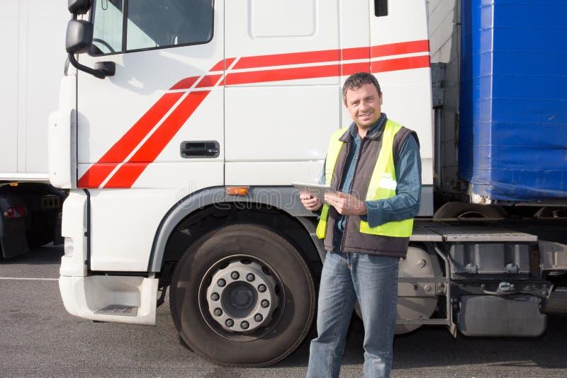 Driver caucasico dell'uomo del camion con la compressa che prepara per la consegna seguente della destinazione fotografie stock