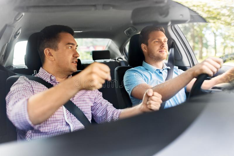 Car driving school instructor teaching male driver royalty free stock photos