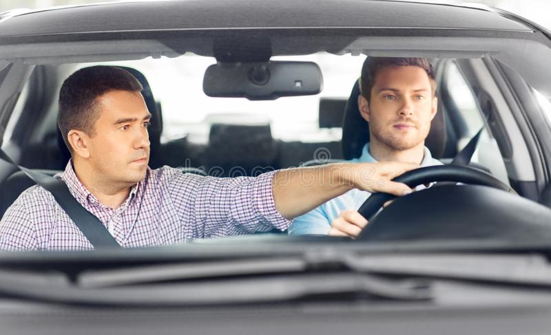 Car driving school instructor teaching male driver. Driver courses and people concept - car driving school instructor teaching young men to drive stock photography