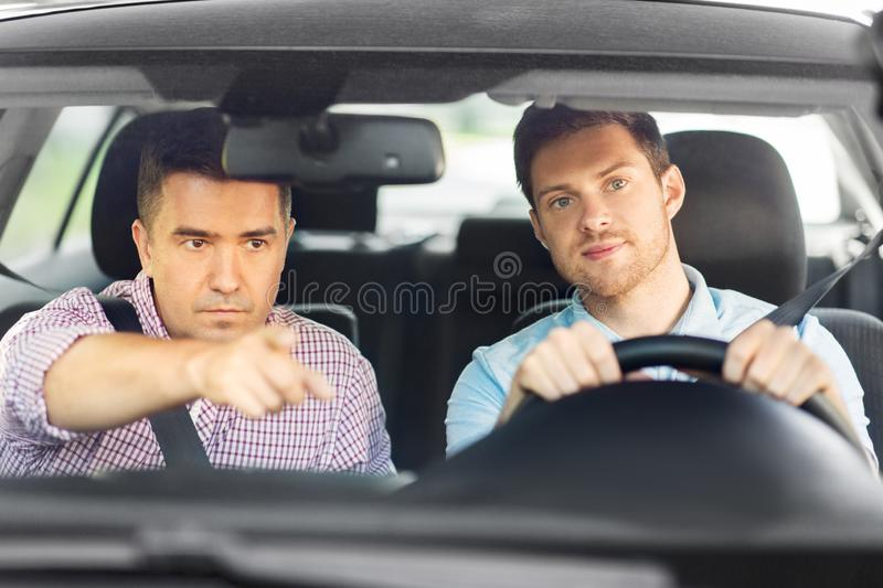 Car driving school instructor teaching male driver. Driver courses and people concept - car driving school instructor teaching young men to drive royalty free stock image