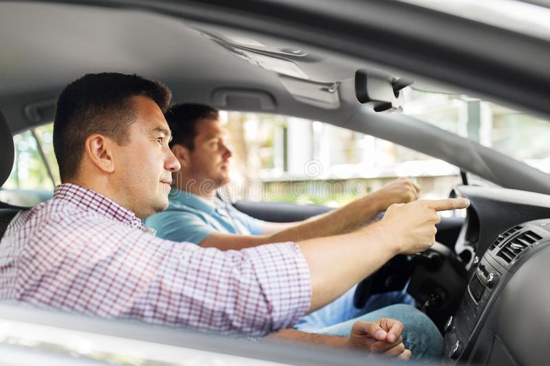Car driving school instructor teaching male driver. Driver courses and people concept - car driving school instructor teaching young men to drive stock images