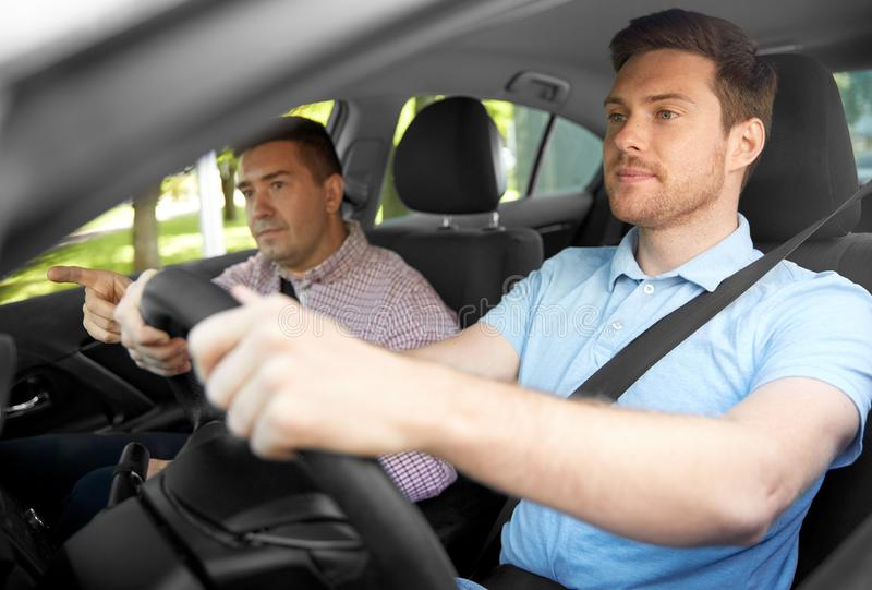 Car driving school instructor teaching male driver. Driver courses and people concept - car driving school instructor teaching young men to drive royalty free stock images