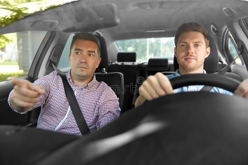 Car driving school instructor teaching male driver. Driver courses and people concept - car driving school instructor teaching young men to drive stock photos