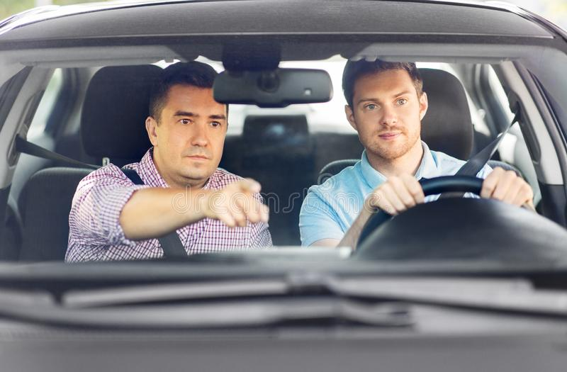 Car driving school instructor teaching male driver royalty free stock image