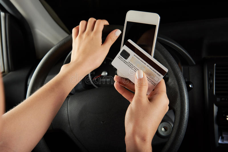 Driver with credit card. Pay with mobile phone stock photo