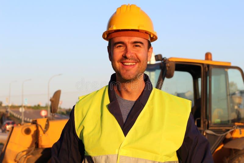 Driver della costruzione con l'escavatore sui precedenti immagine stock