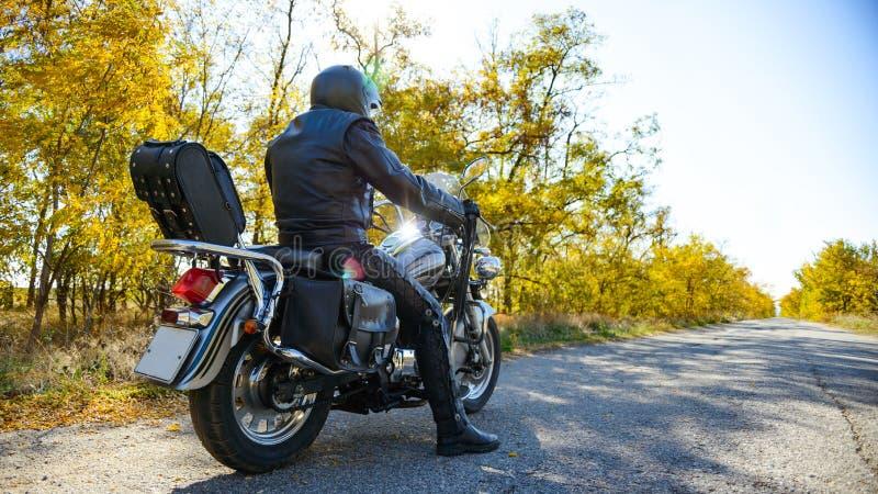 Driver di motociclo Riding Custom Chopper Bike su Autumn Road Concetto di avventura e di viaggio fotografia stock libera da diritti