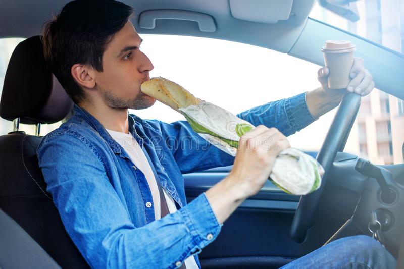 Young hungry businessman eating junk food in car stock image