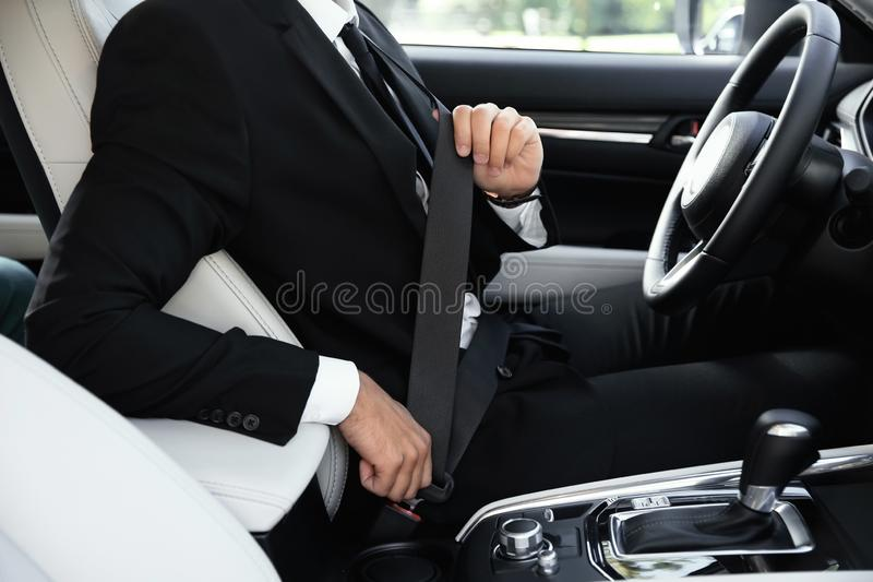 Driver fastening safety belt in luxury car, focus. On hands royalty free stock images
