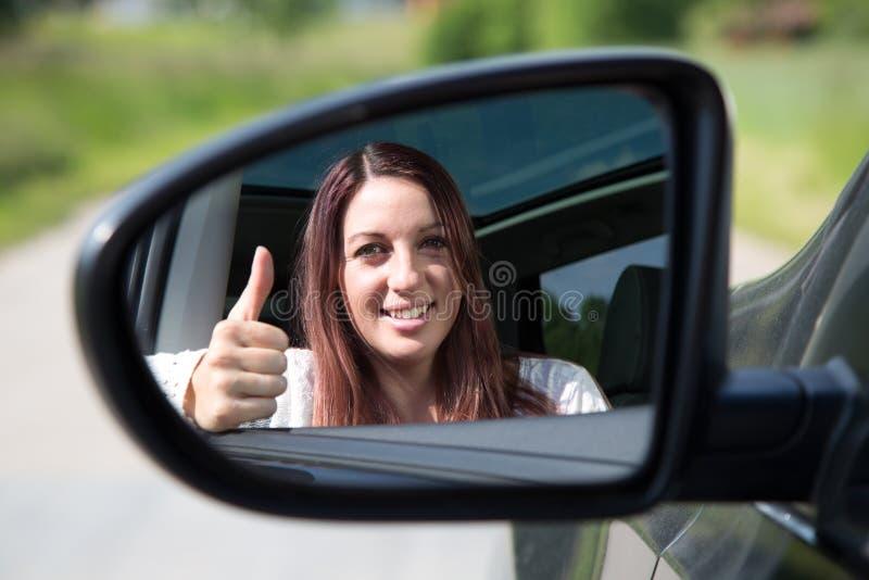 Driver felice che mostra i pollici su nello specchio immagine stock
