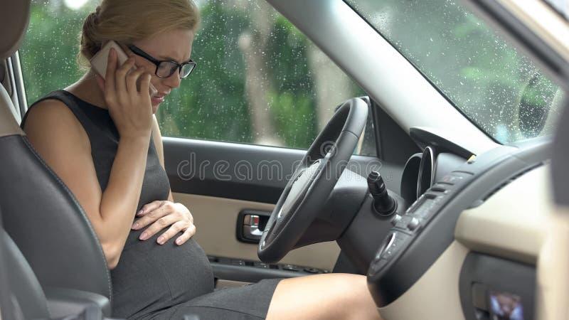 Driver femminile che ha problemi di gravidanza che chiamano 911, pronto soccorso, rischio di misbirth immagini stock libere da diritti