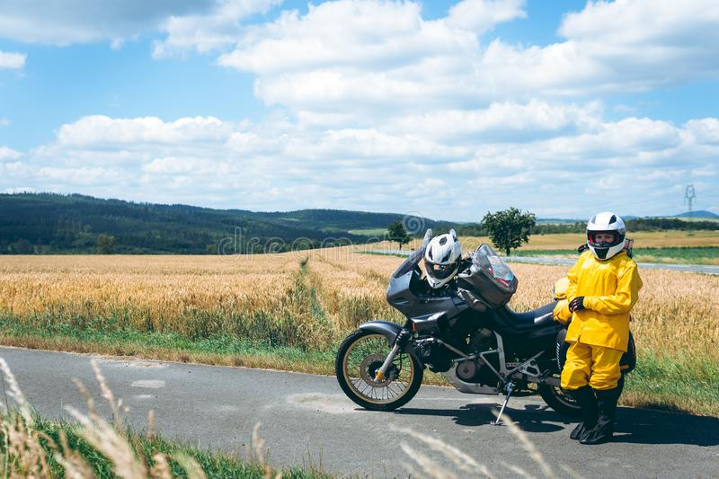 The driver girl in the helmet is wearing a raincoat. Adventure motorbike with side bags. a motorcycle tour journey. Outdoor. World. Travel on two wheels stock image