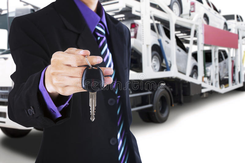 Driver giving a car key with trailer truck background. Male driver wearing formal suit and gives a car key with the trailer truck background carrying new cars stock photography