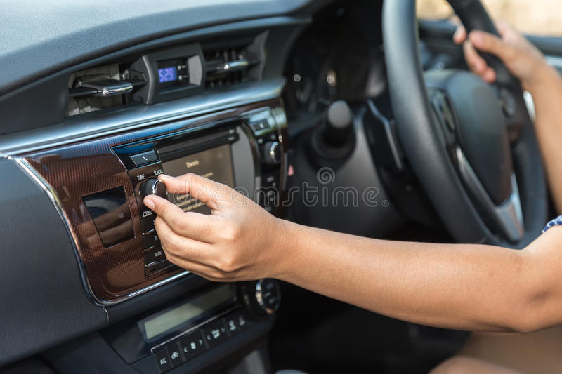 Driver hand adjust audio button in the car stock images