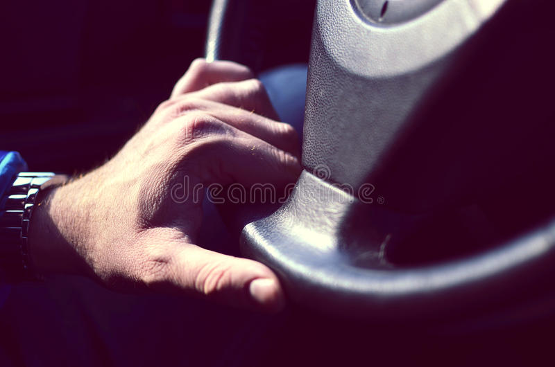 Driver hands holding steering wheel. Male driver hands holding steering Wheel and driving royalty free stock image